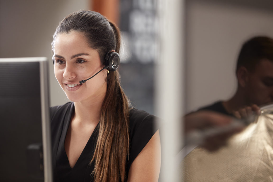 female customer services agent working at desk in ZJ2P9SC 1