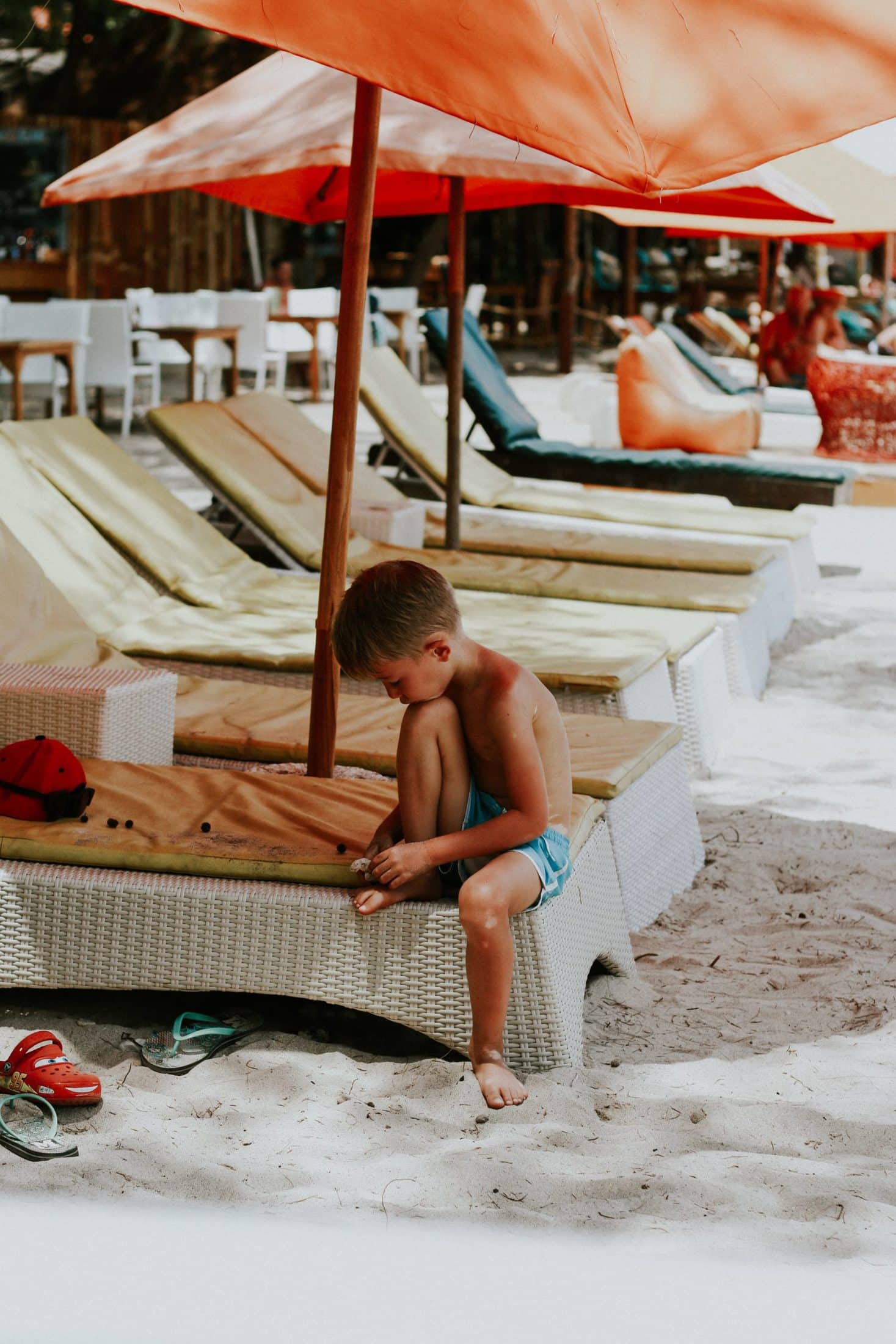boy sitting on white wicker chaise lounge on beach