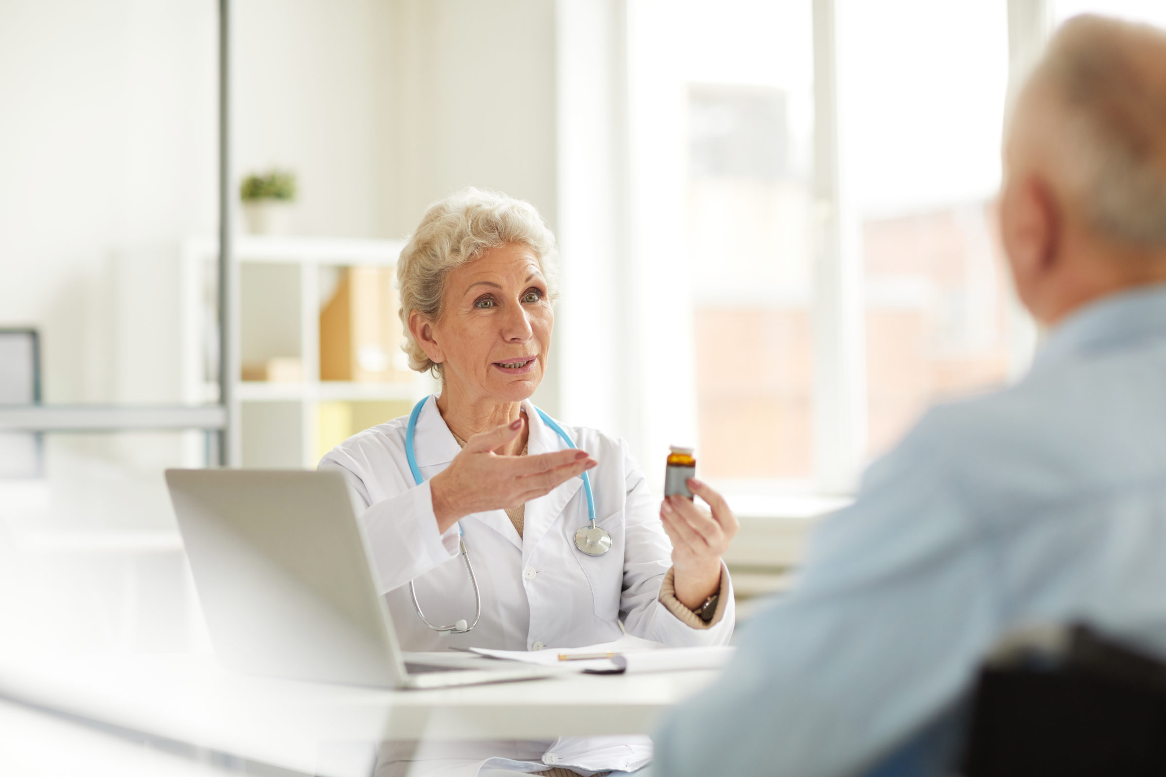 senior doctor offering pills CF2SXU4