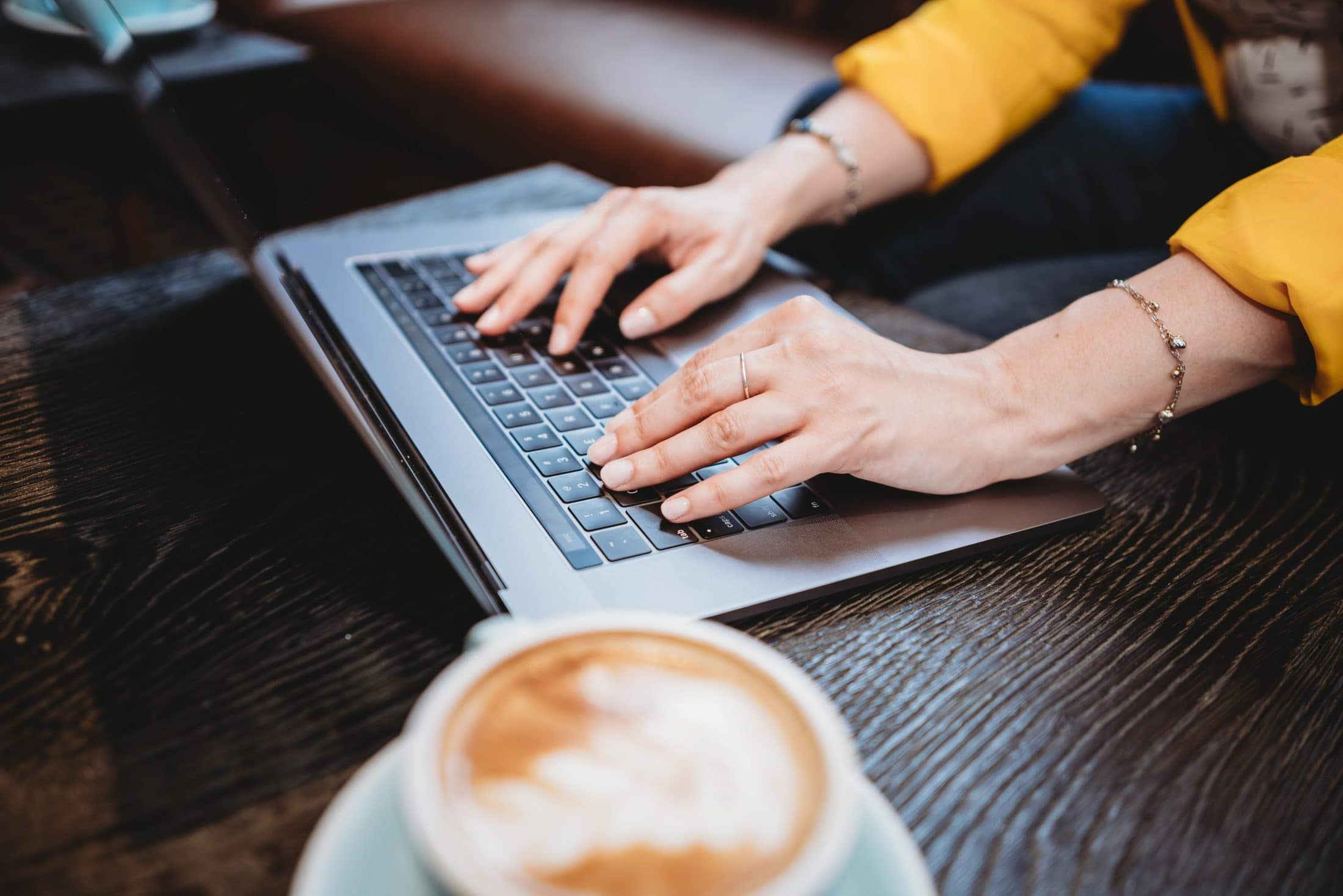 person using macbook pro on brown wooden table