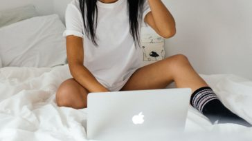 woman wearing white crew-neck t-shirt on bed holding silver MacBook