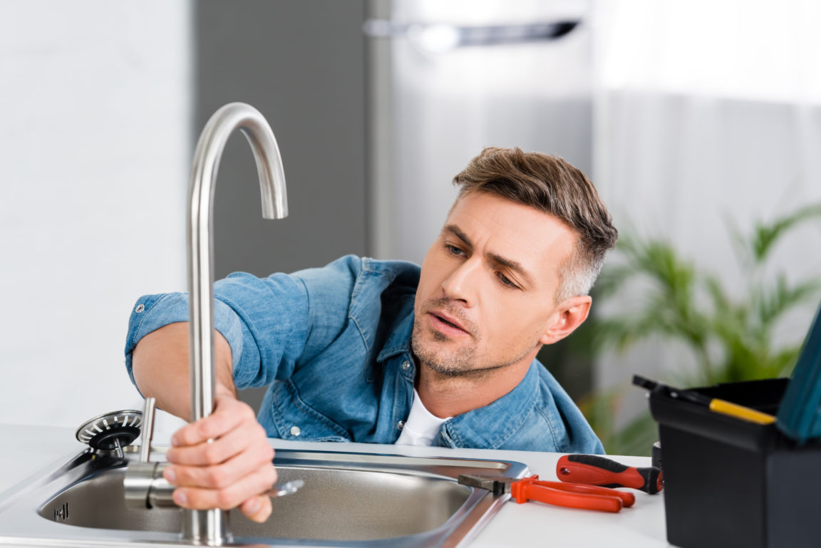 handsome man repairing faucet of kitchen sink 43SSC7W