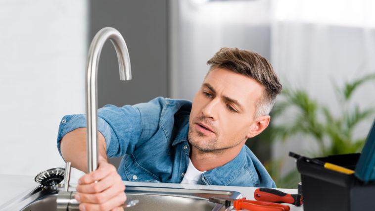 handsome man repairing faucet of kitchen sink 43SSC7W