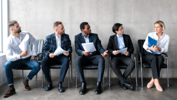 men staring at woman applicant waiting for job int 9XQWENF