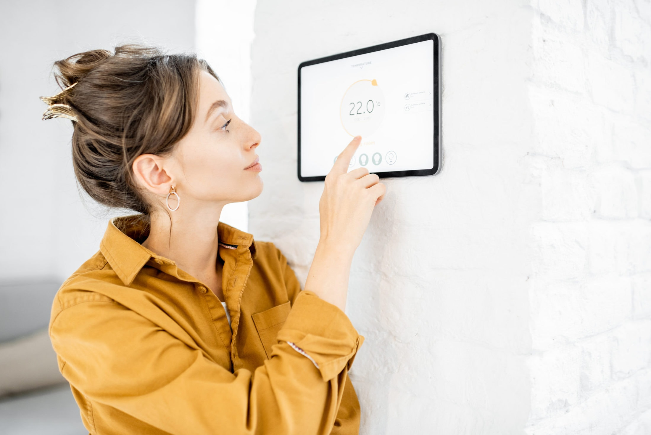 woman controlling room temperature with a digital KXDE64T scaled