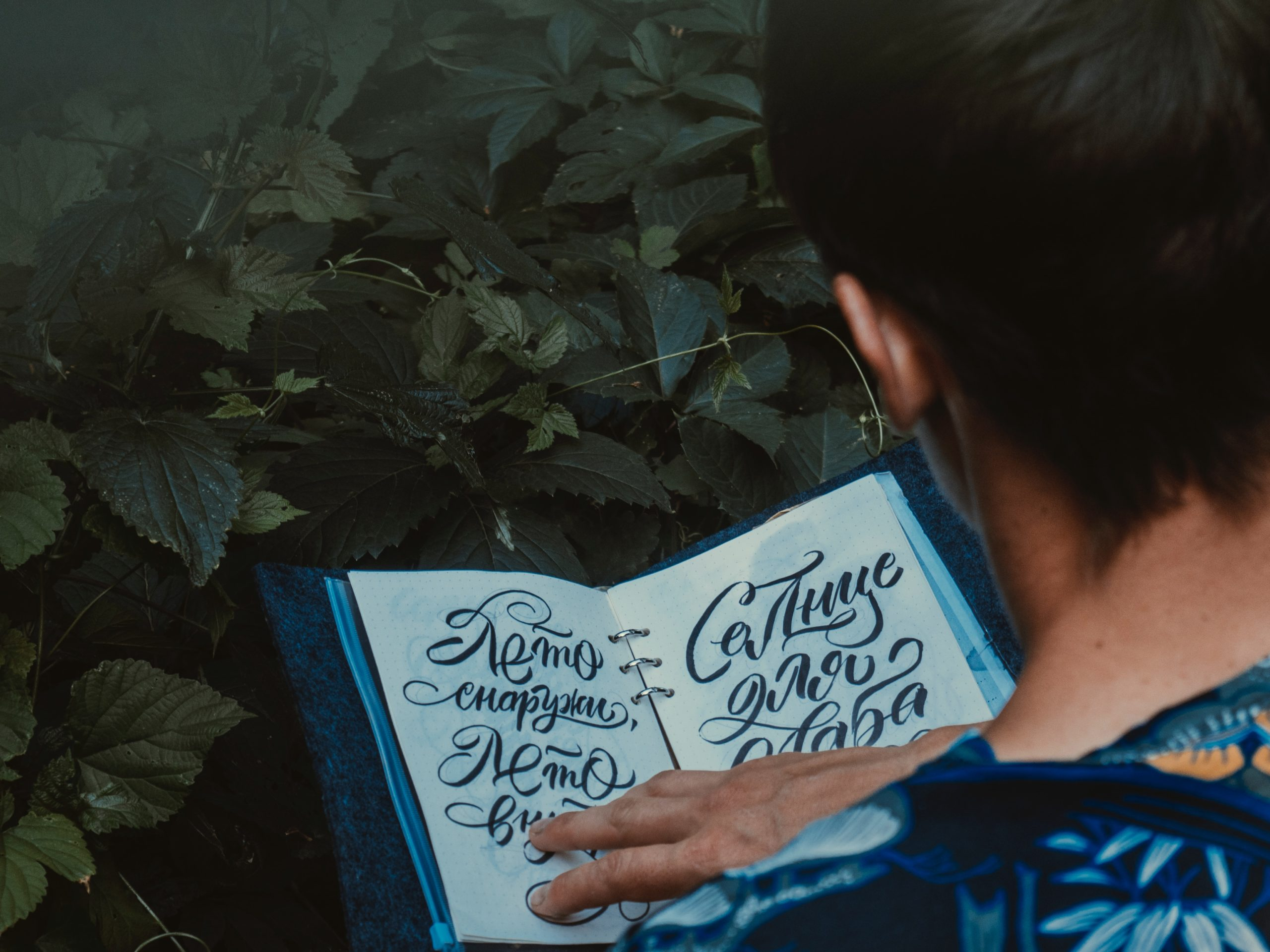 person in blue and white floral shirt reading a book