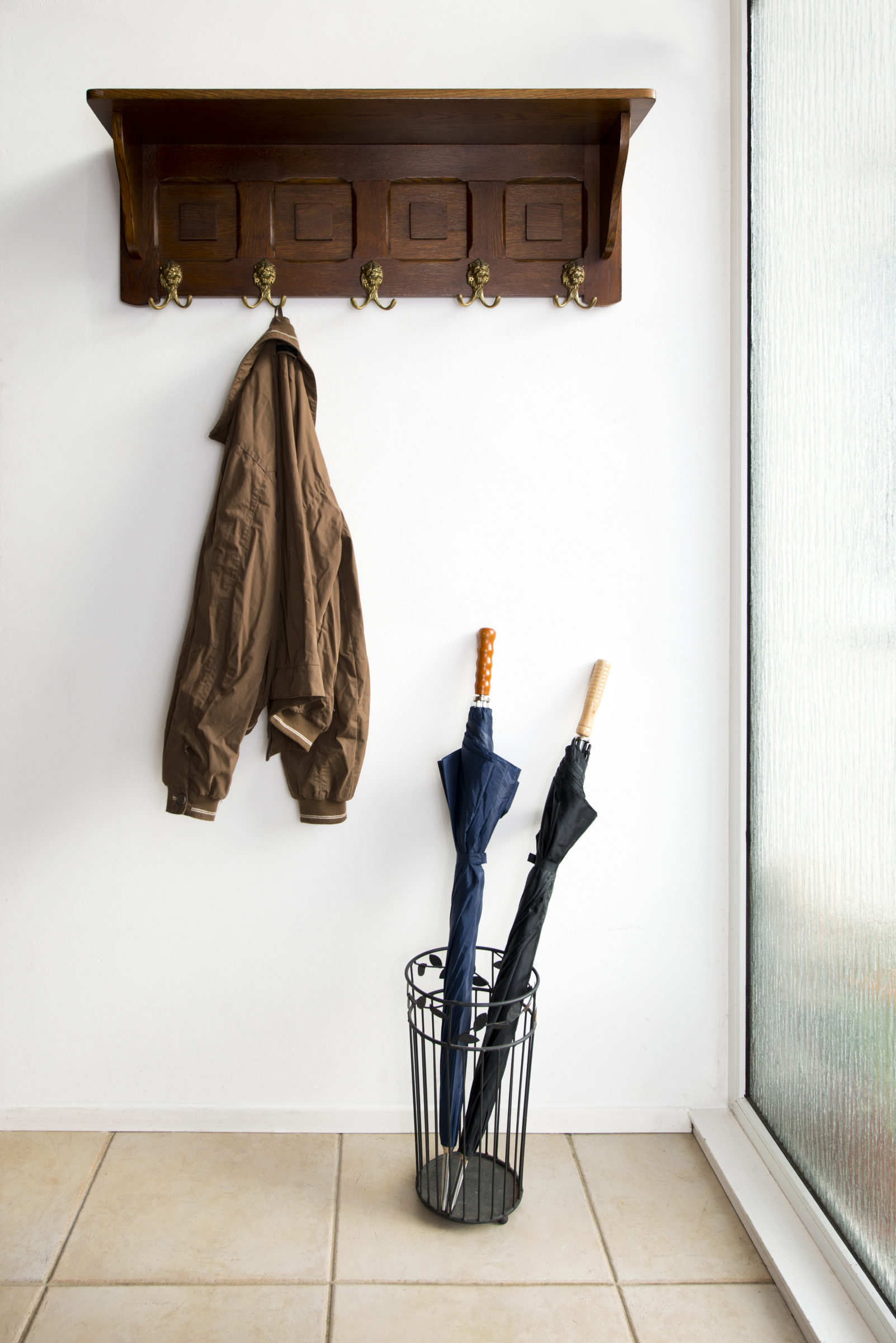 54185 jacket and umbrellas in foyer of home M2NGDVQ