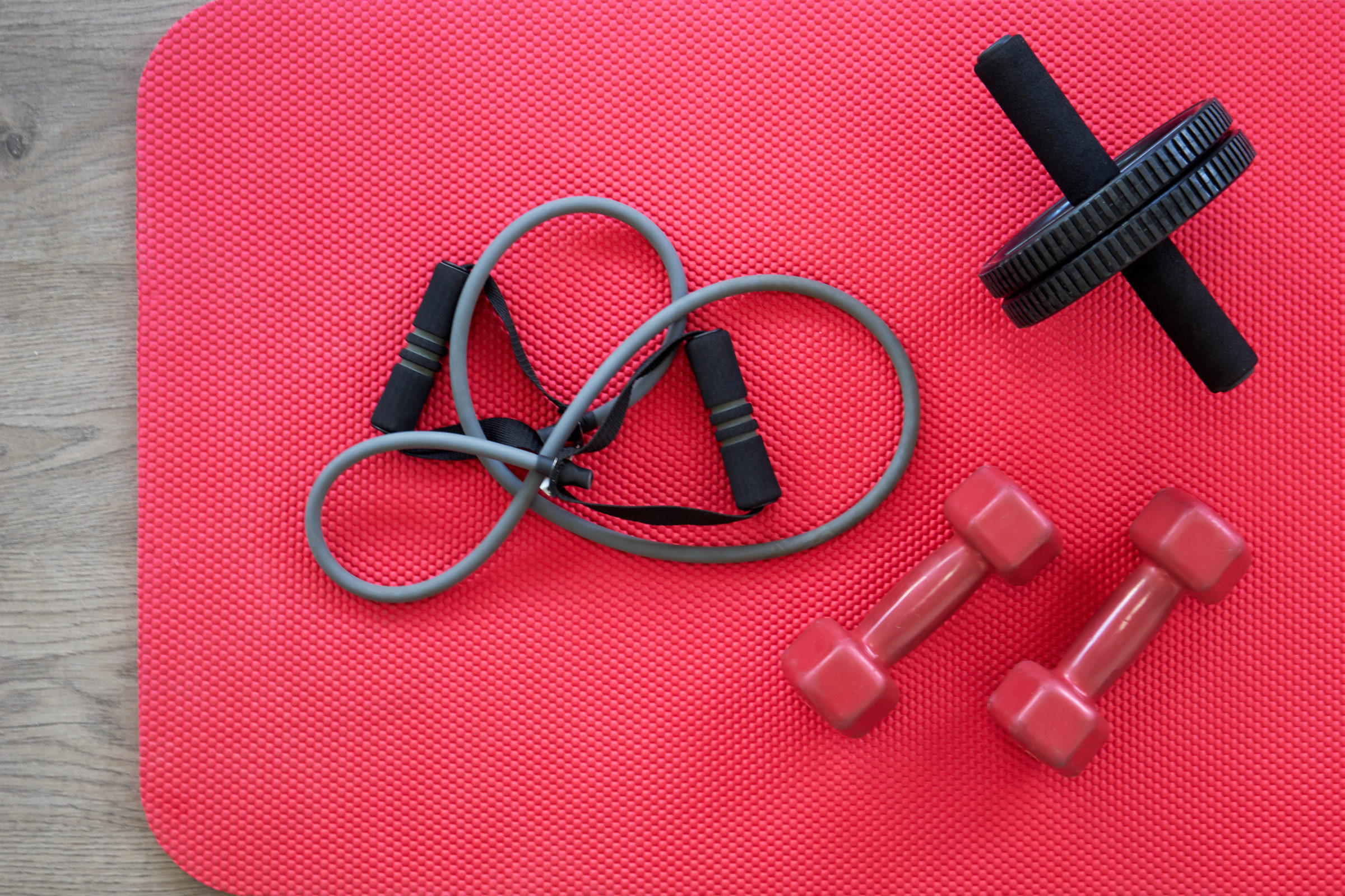 gym equipment on red mat as background top view PLBAEVD