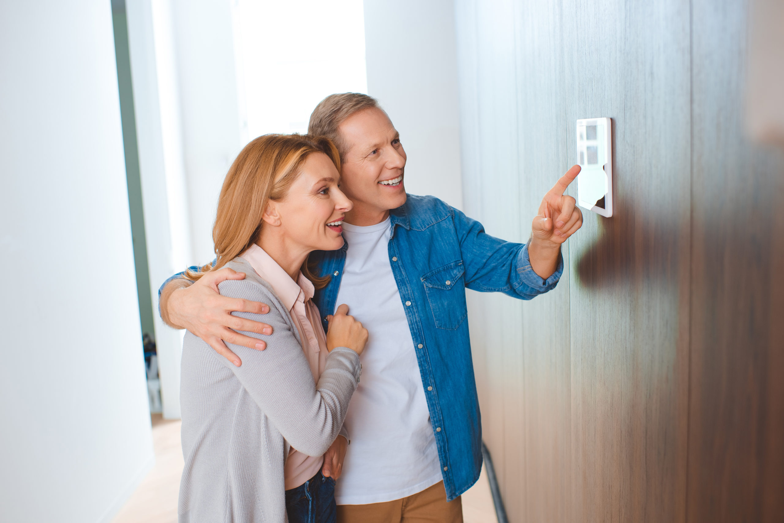 happy man pointing at smart home control panel whi V2PLF9C scaled
