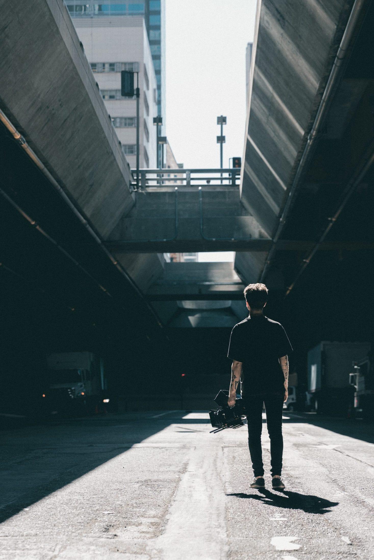 man walking under the bridge
