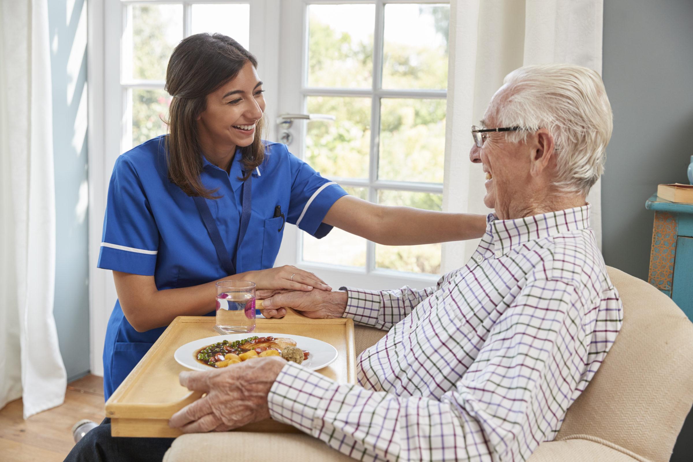 nurse serving dinner to a senior man in an armchai PHNDR42