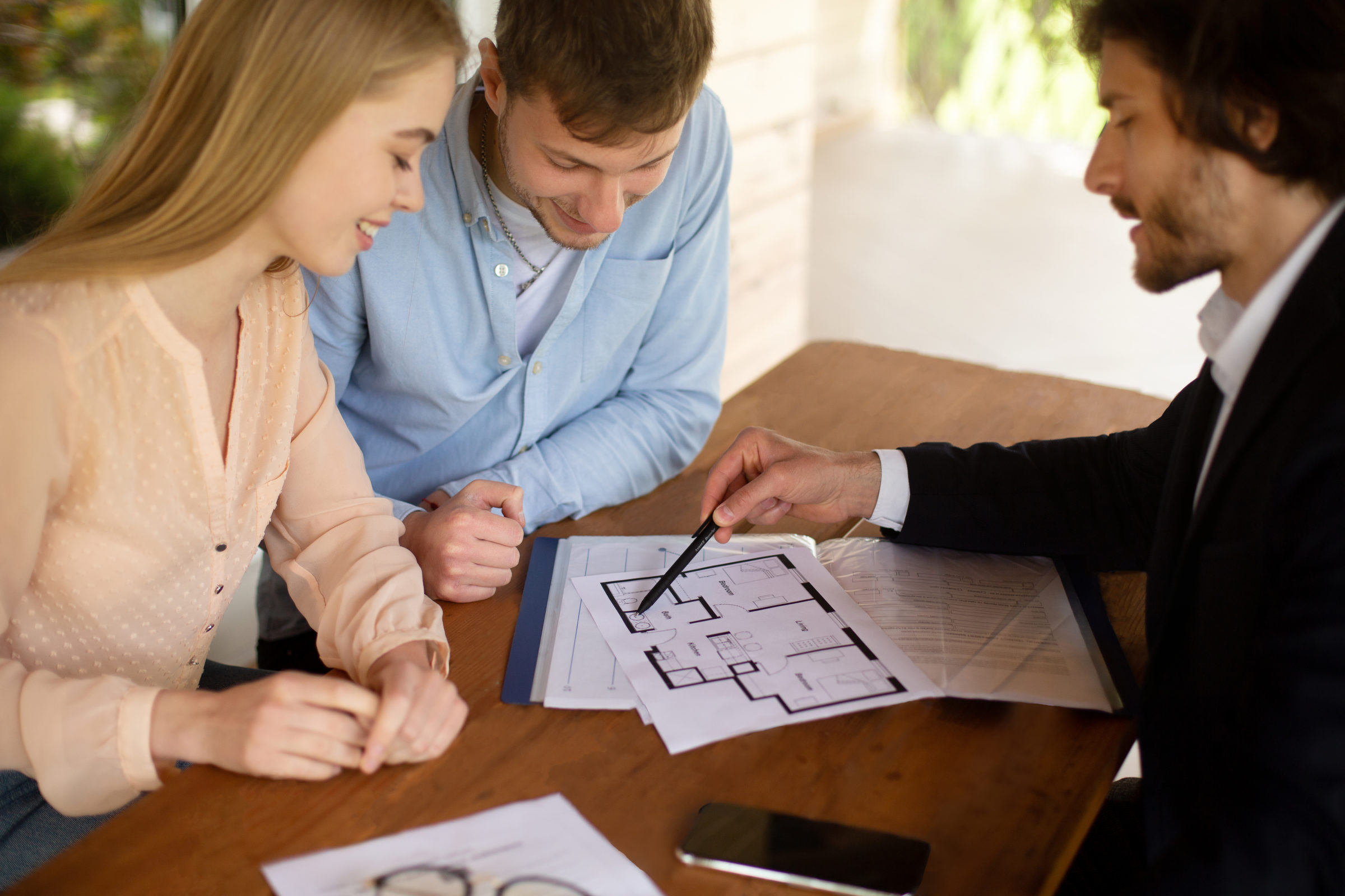 realtor showing blueprint of new home to happy cou AYGGZ2W