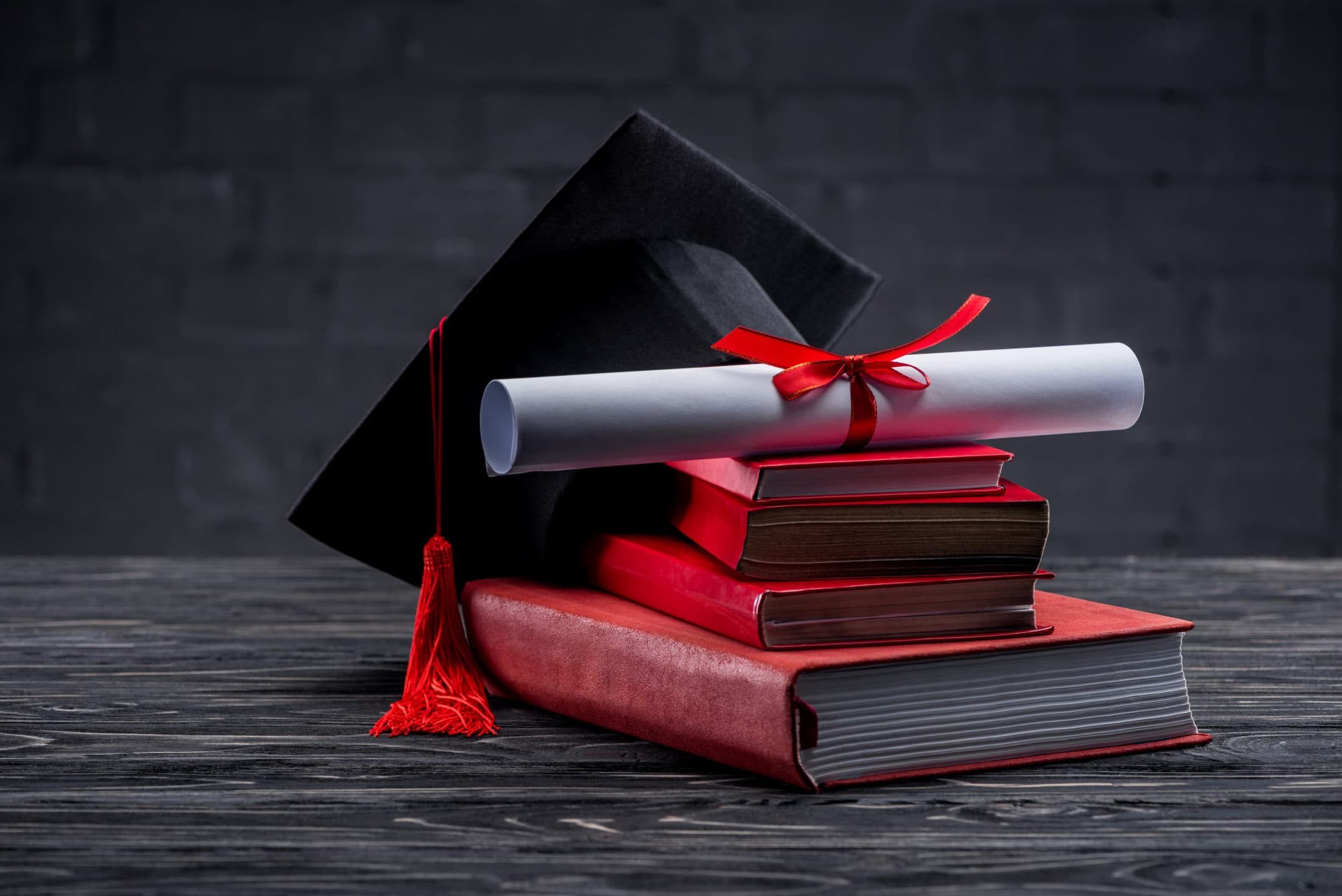 stack of books with diploma and graduation hat on CY6ZRAY scaled