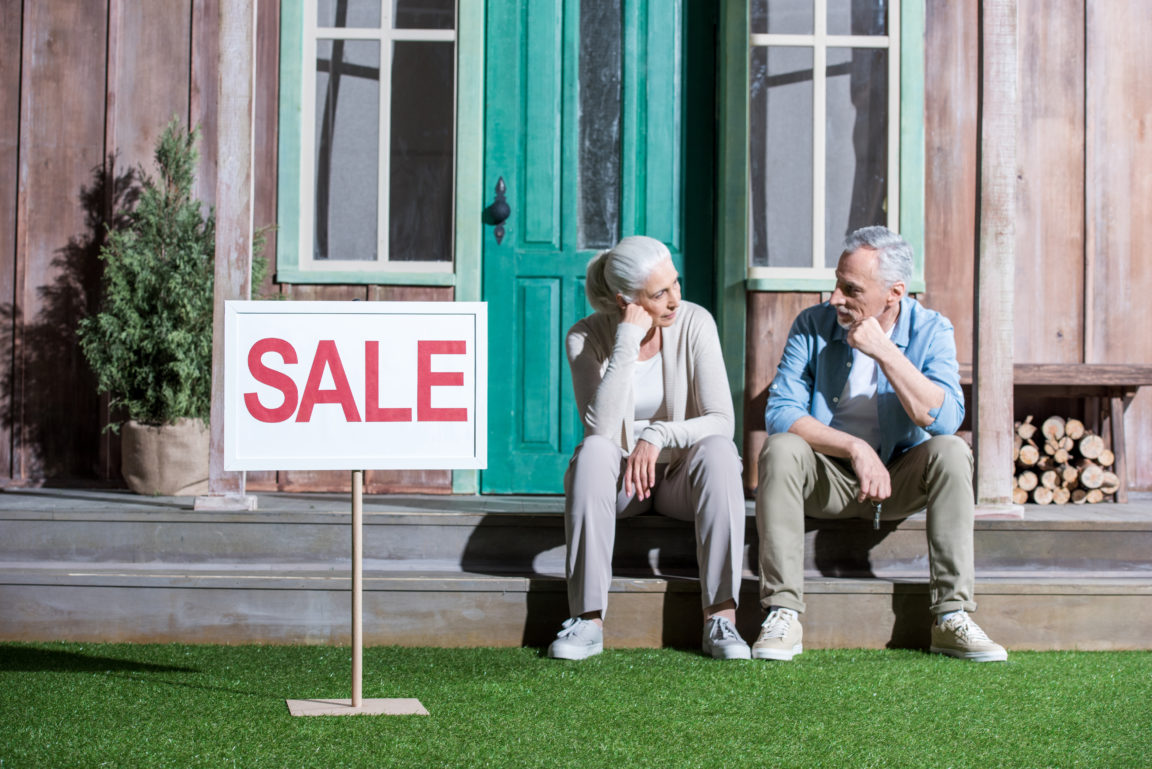 upset senior couple sitting on porch and selling t SCDW498