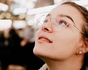 selective focus photography of woman wearing eyeglasses looking up