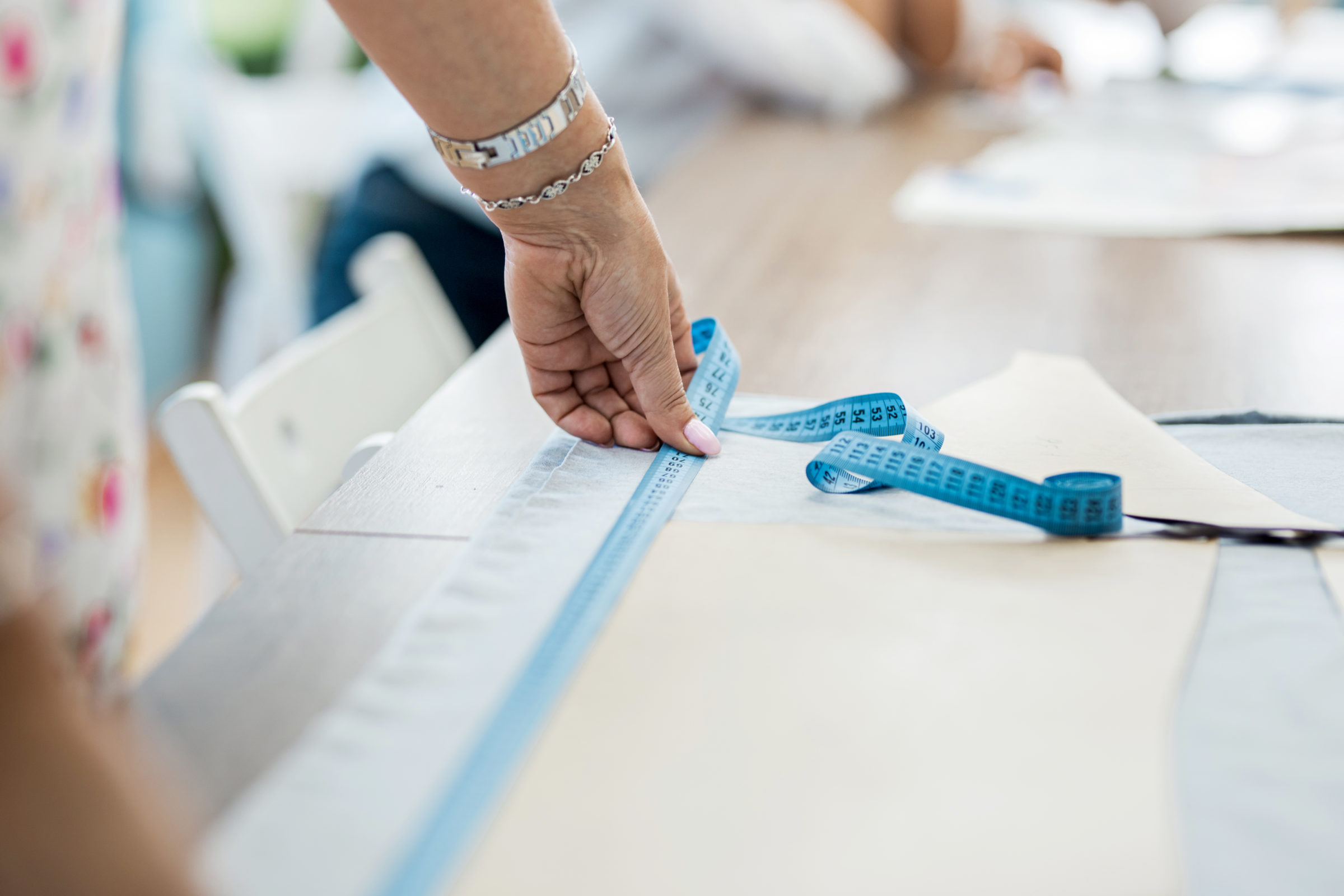 a woman with a bracelet is measuring fabric fashio XRAQ8L9