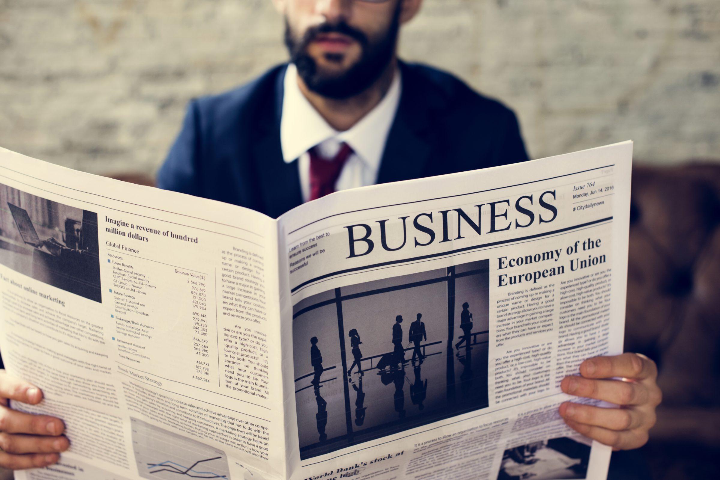 businessman reading newspaper PQLRSAV