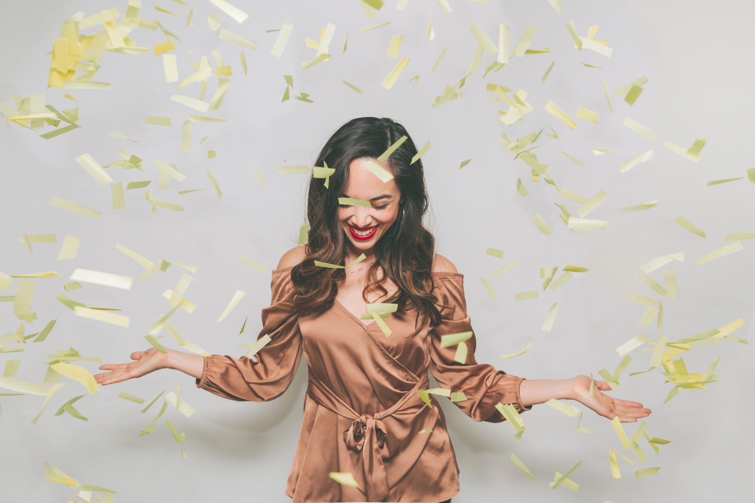 confetti falling on a woman dressed in gold NBWVCQ4