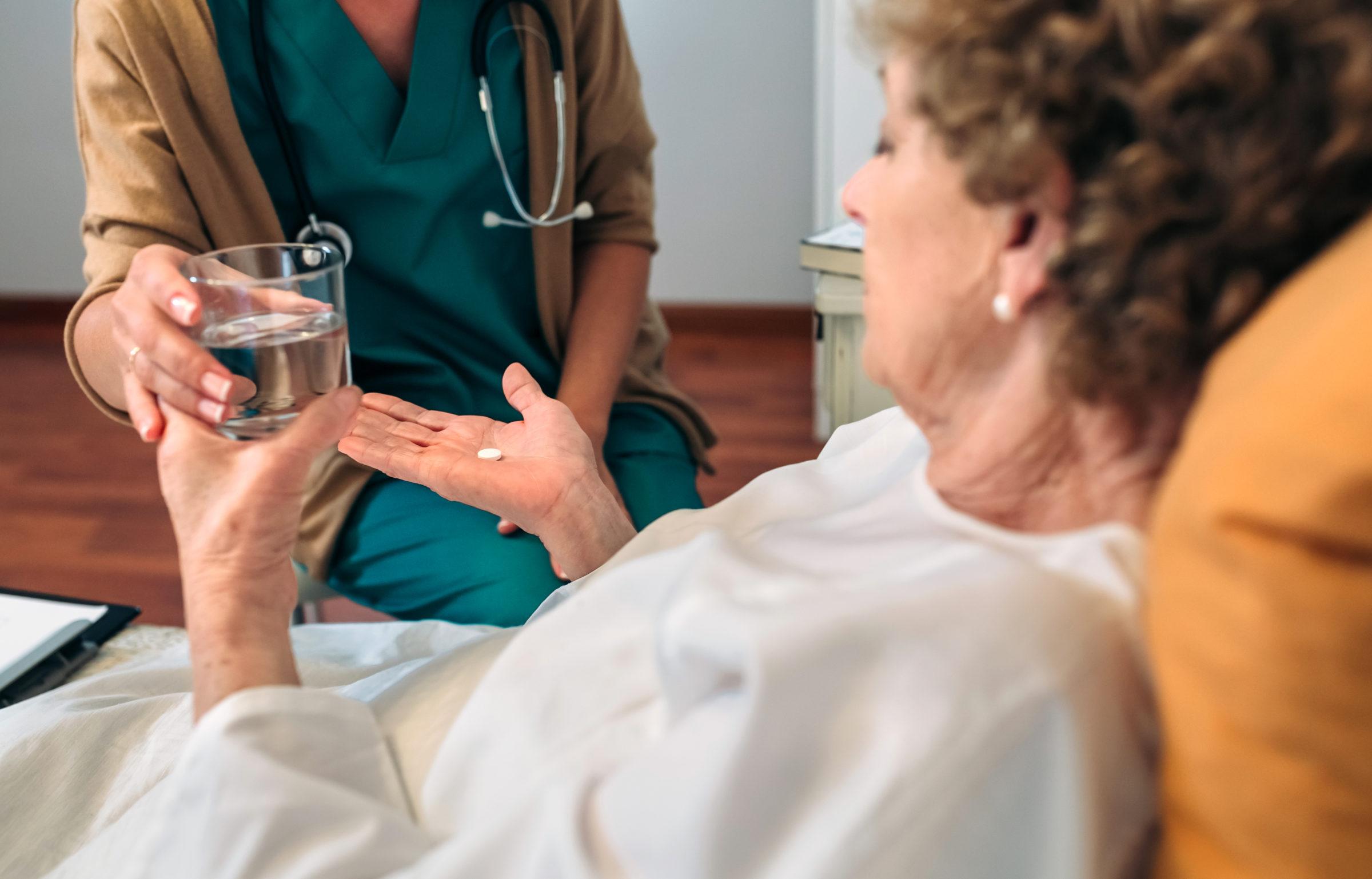 doctor giving medication dose to elderly patient BNDR4JD