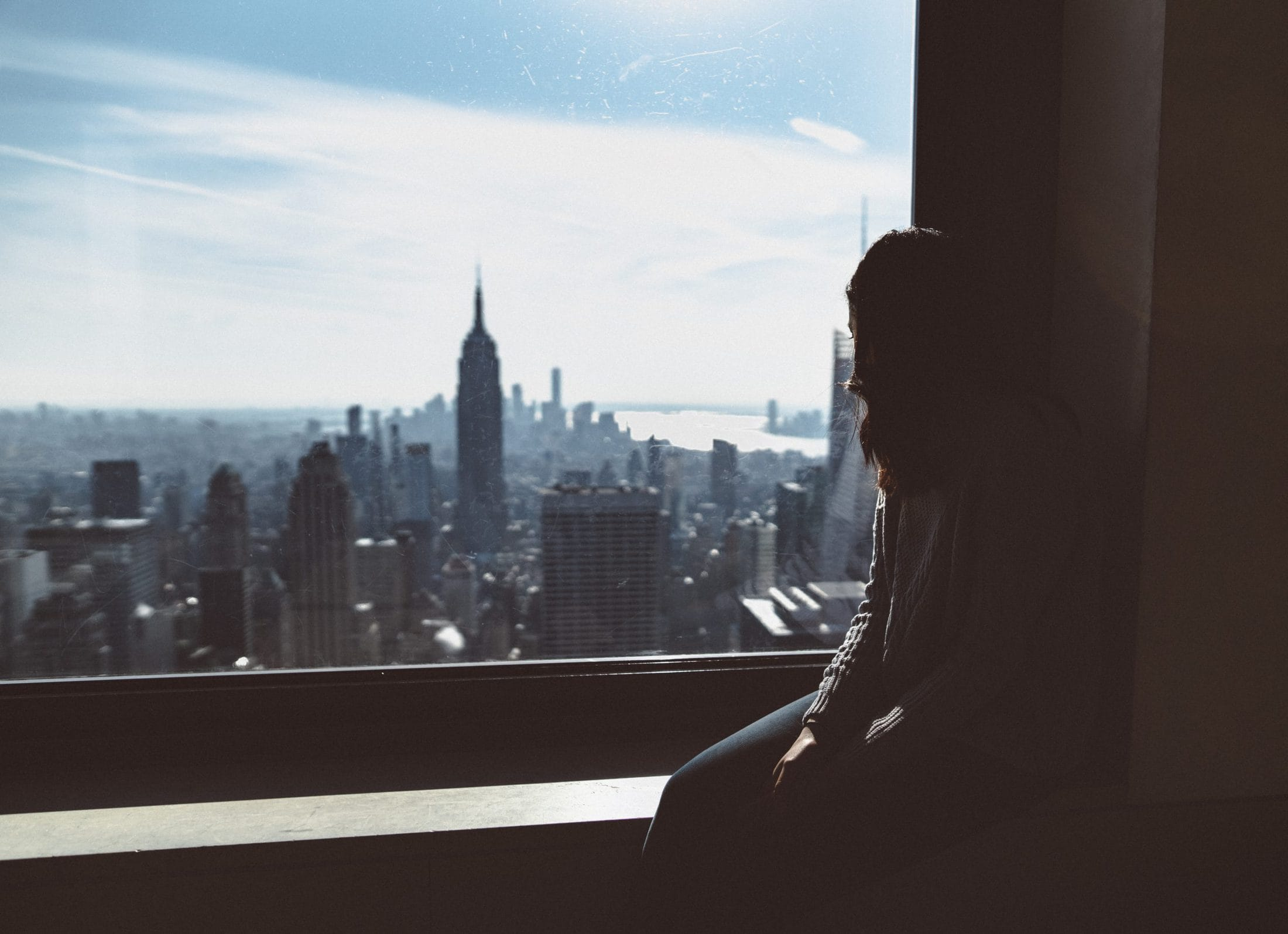 woman sitting on window edge looking at Empire State tower