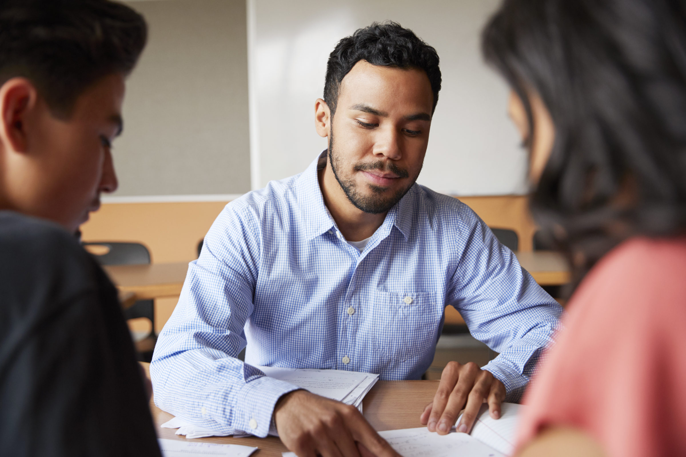 male high school tutor with two students at desk i CMW5F82