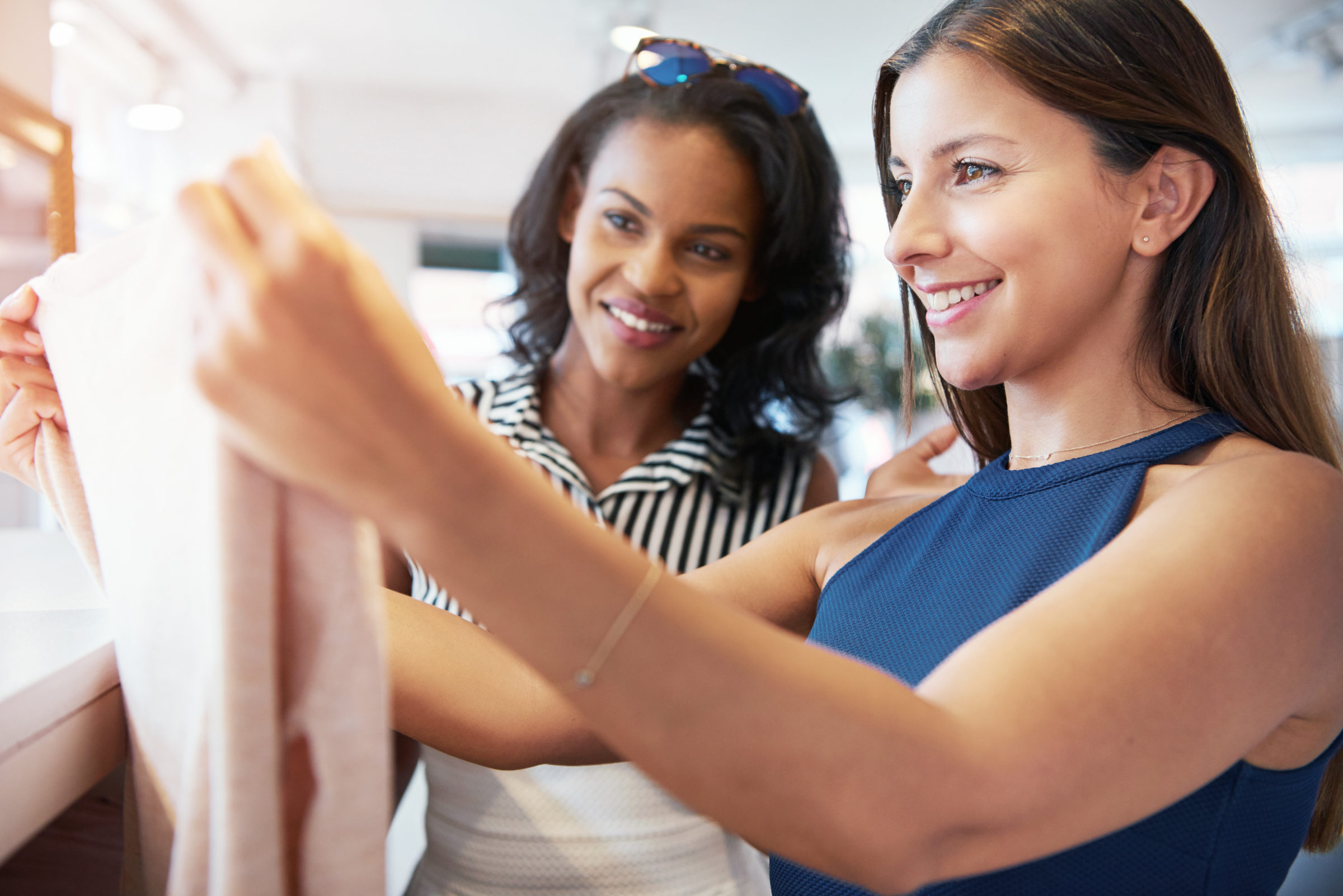 two young female friends shopping for clothes A65QUBR