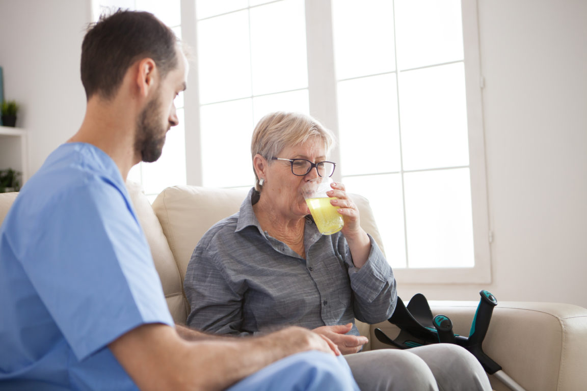 young caregiver sitting down on couch with senior QTNBSQF