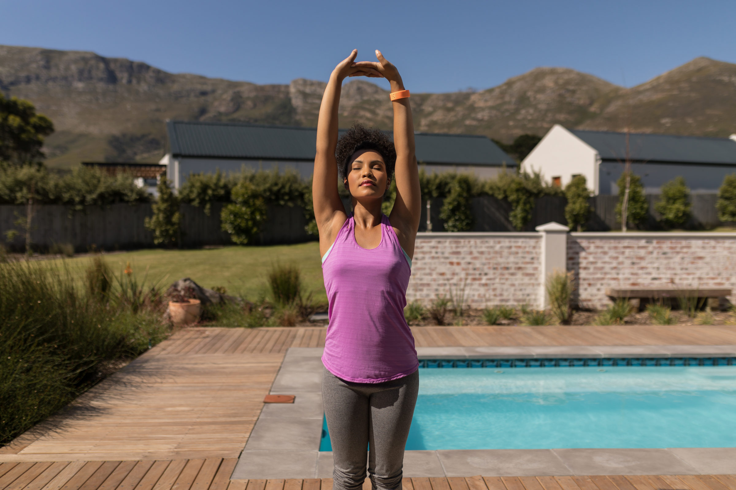 young woman performing yoga next to the swimming p D9JY6L4