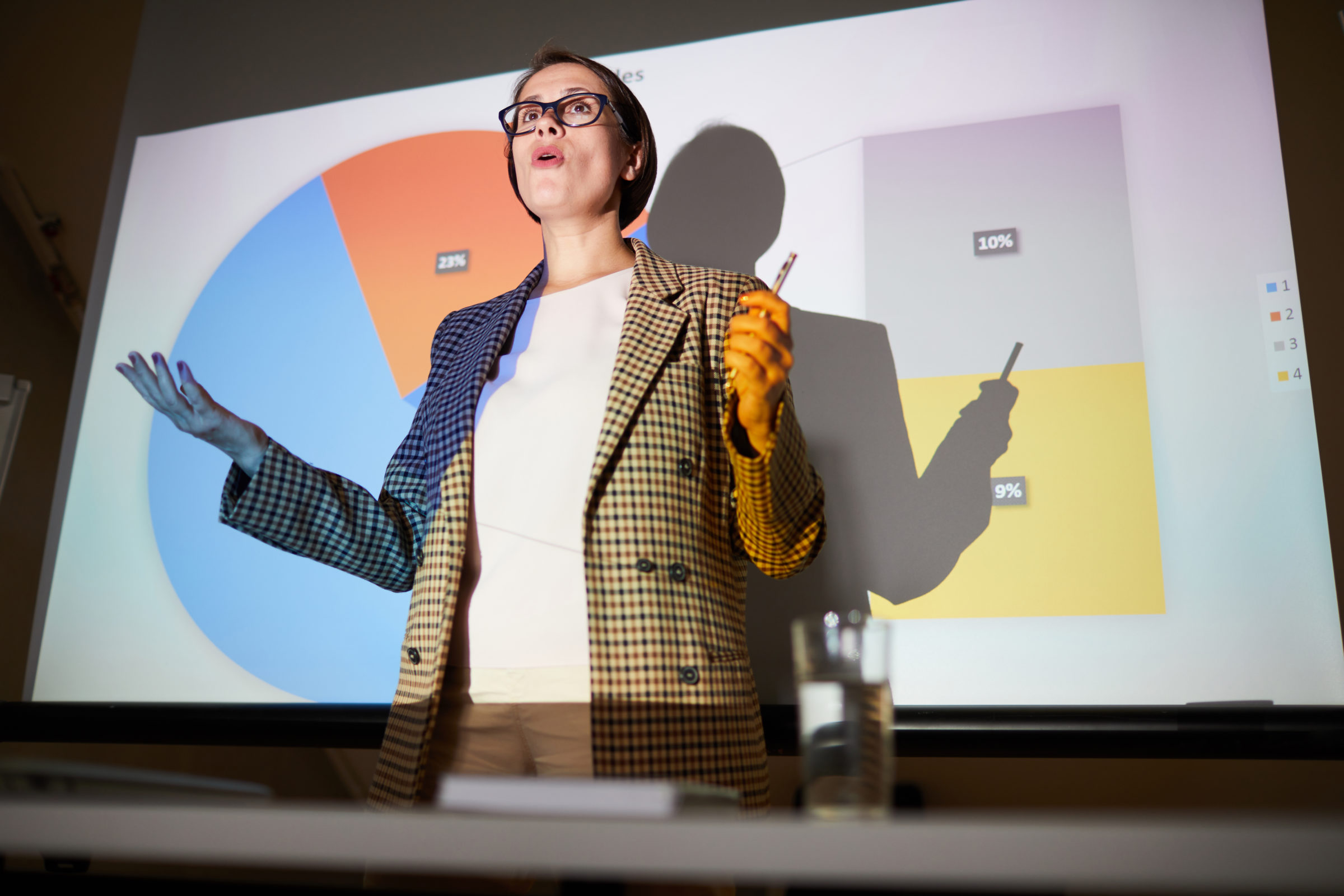 confident lady explaining data on projection scree 7HJMCVN