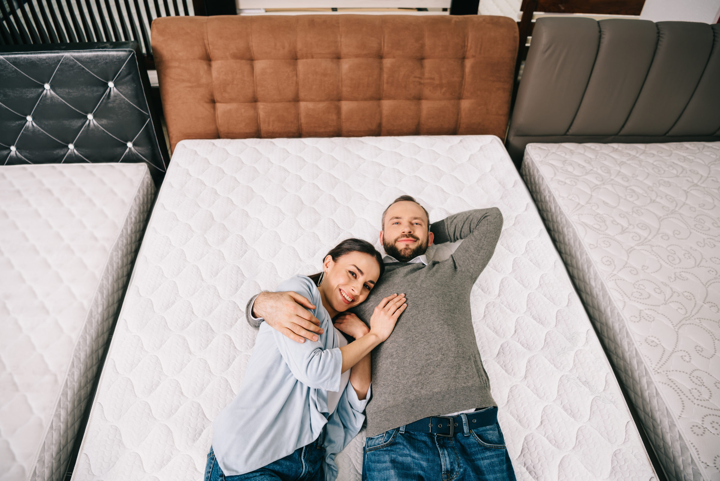 overhead view of smiling couple lying on bed in fu 5ZH5WM6