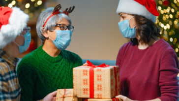 people with gifts wearing facemasks on christmas NP774VV