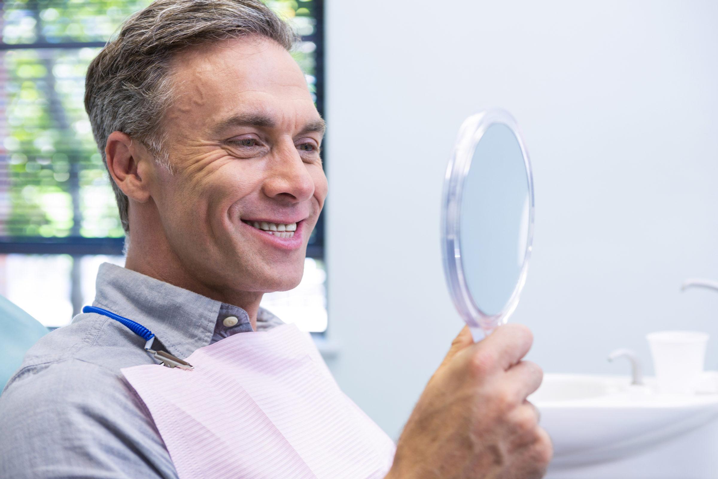 portrait of smiling man looking in mirror Z48RRTA