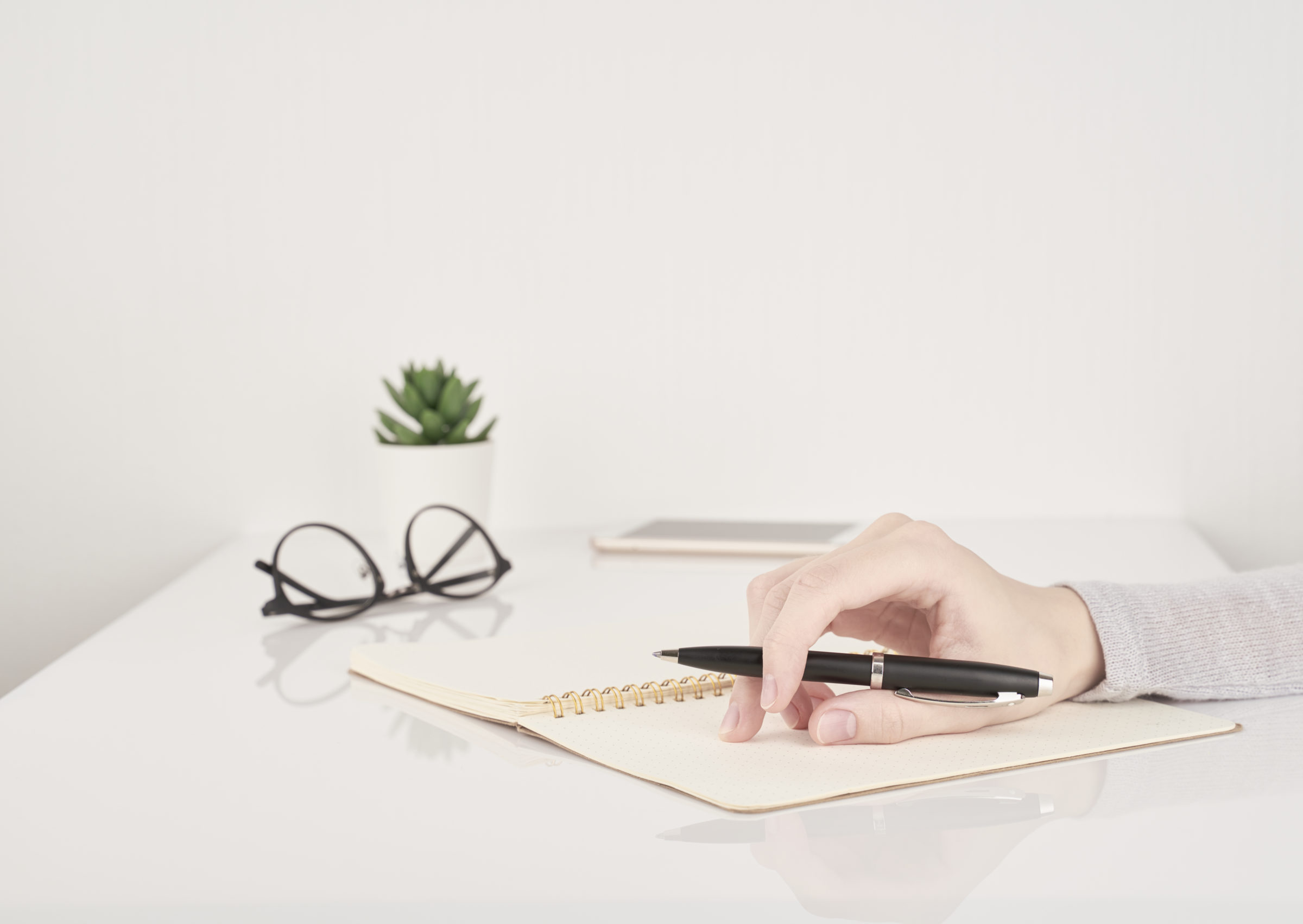 woman writing on notebook page office work or stud A7VM3BQ