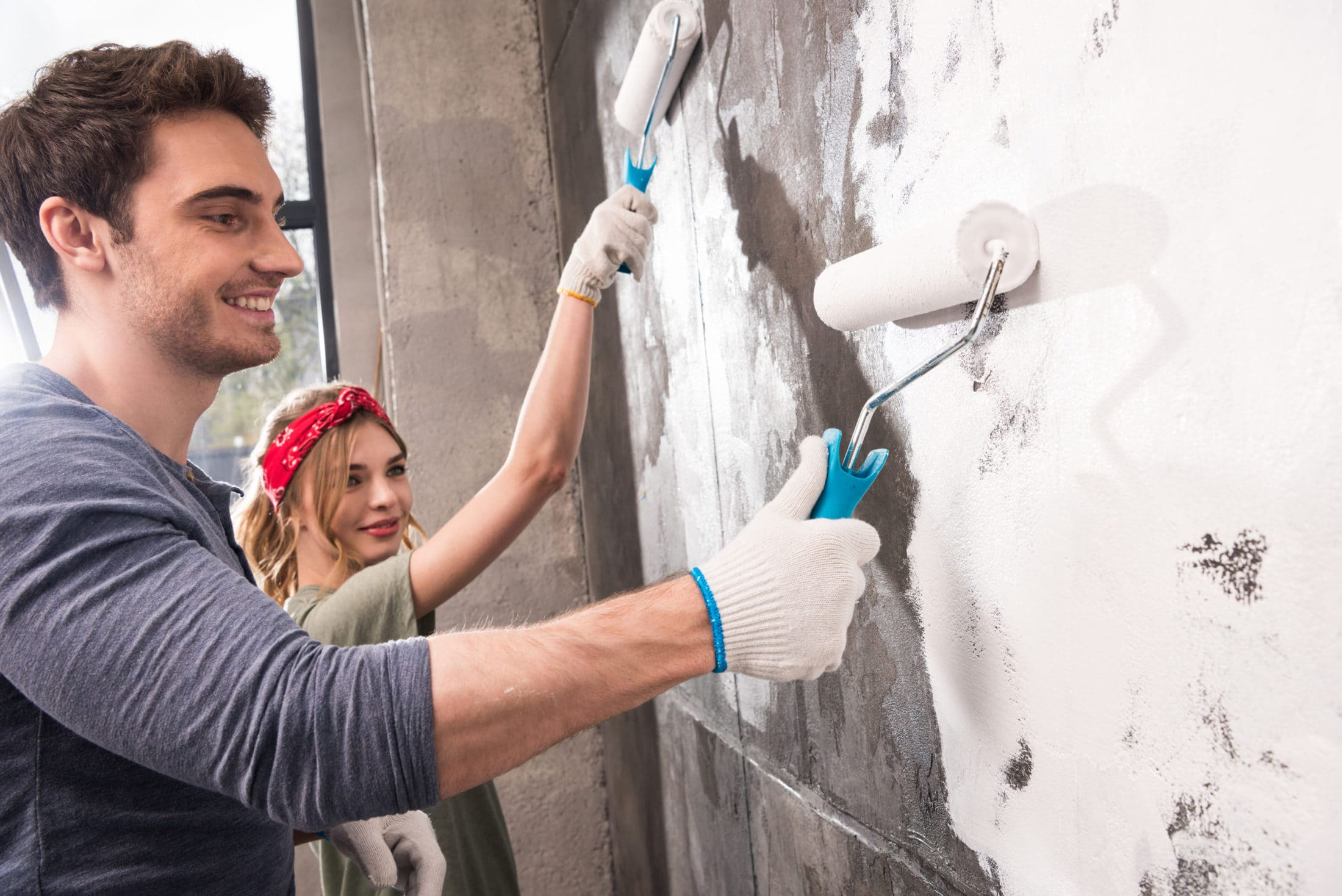 young couple painting wall together renovation hom U84J3P8 scaled