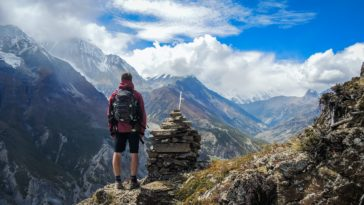 man standing on top of mountain beside cairn stones