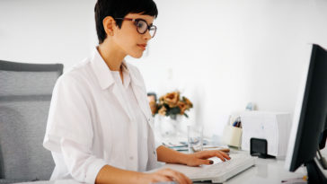 beautiful female doctor typing receipt for patient UEJN8Y5