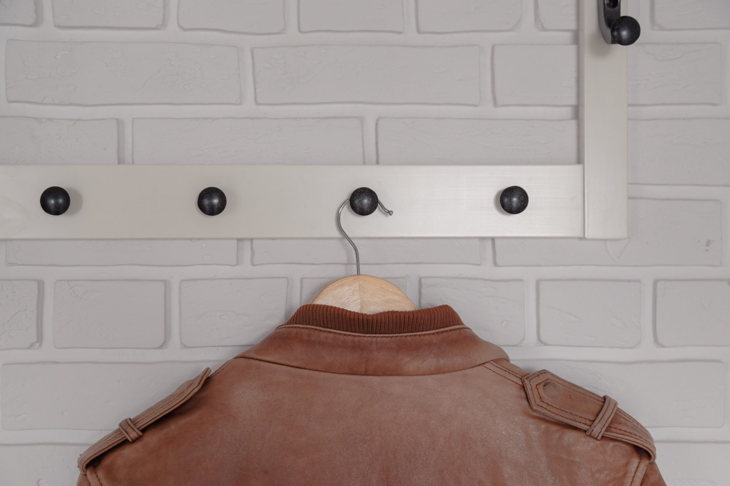 brown leather jacket hanged on white wall hanger GB7PU42