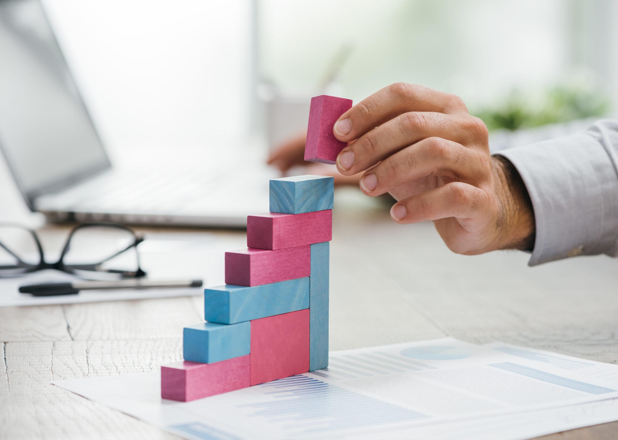 businessman building a growing financial graph P977PUV