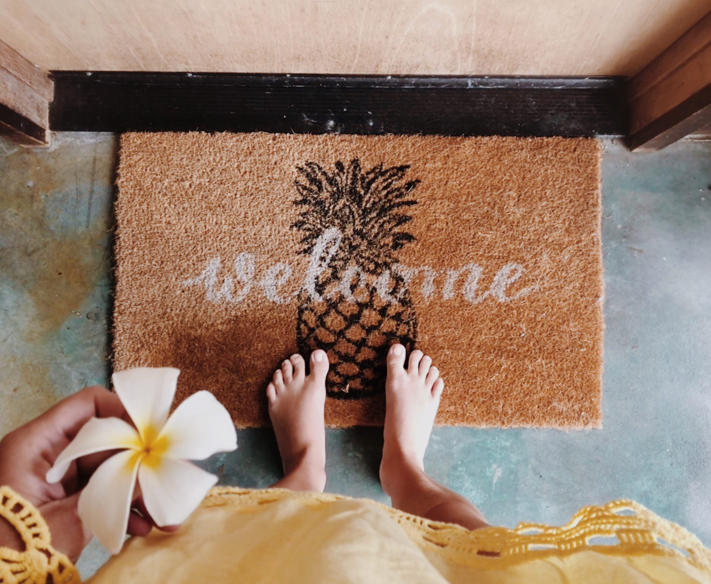woman standing on the door mat with a welcome writ MG5X26C
