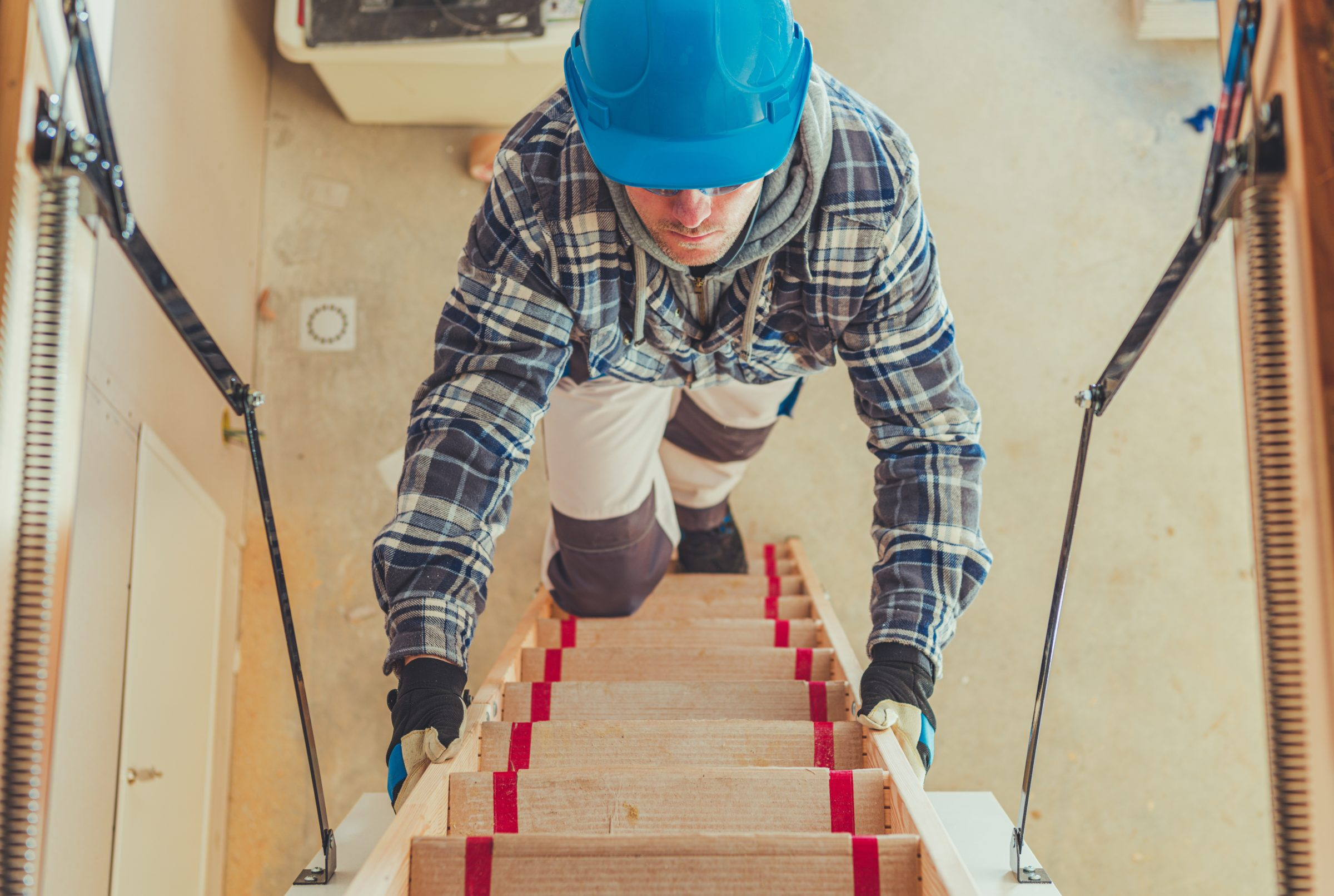 worker climbing on attic stairs Q9X6LEE