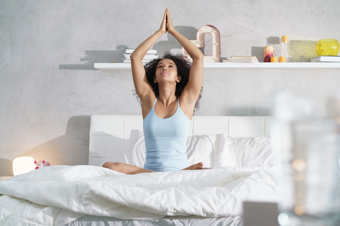 young african american woman doing yoga in bed aft 6M948W2