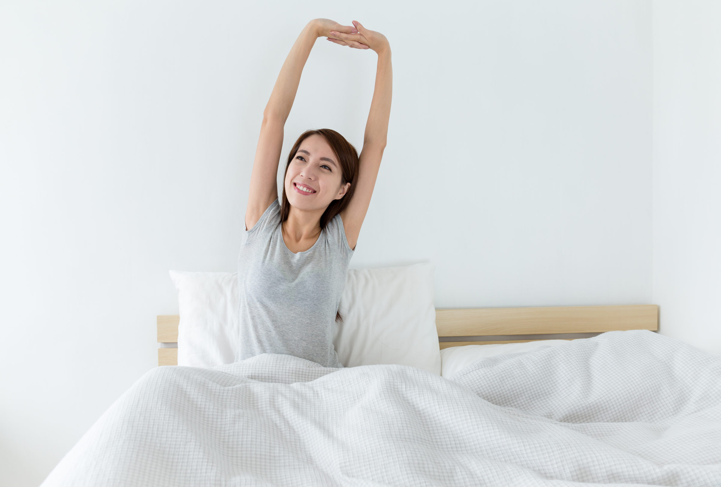 young woman waking up happily after a good night s PRWBHNL