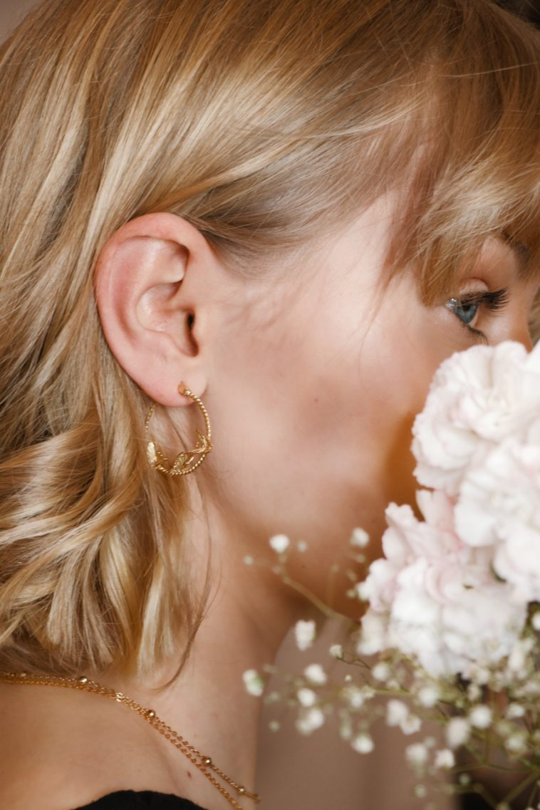 woman with blonde hair wearing gold earrings