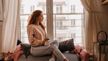 pensive ginger girl in jeans drinking coffee in he JATLU4X
