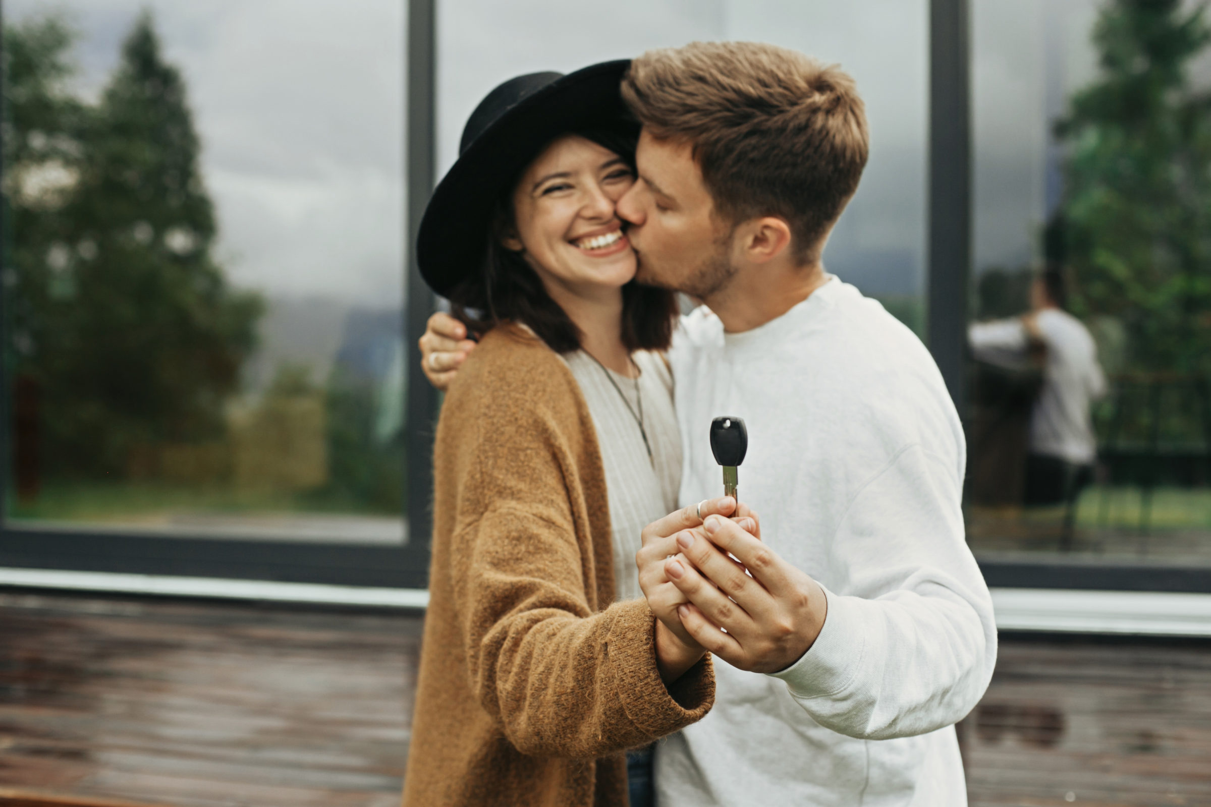 stylish hipster couple holding together key from t 3YD27L5 1
