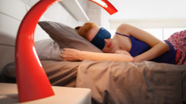 woman in bed sleeping with sleep mask on eyes PLEJY5M