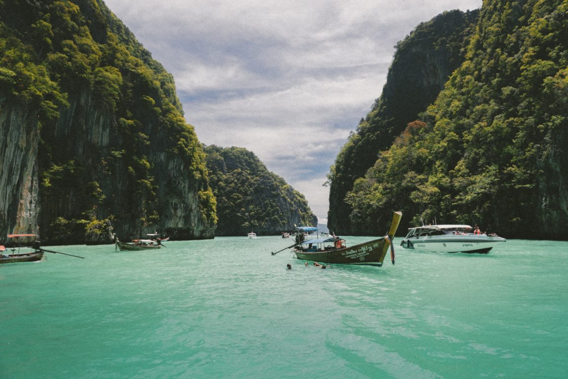 four wooden boat on teal sea