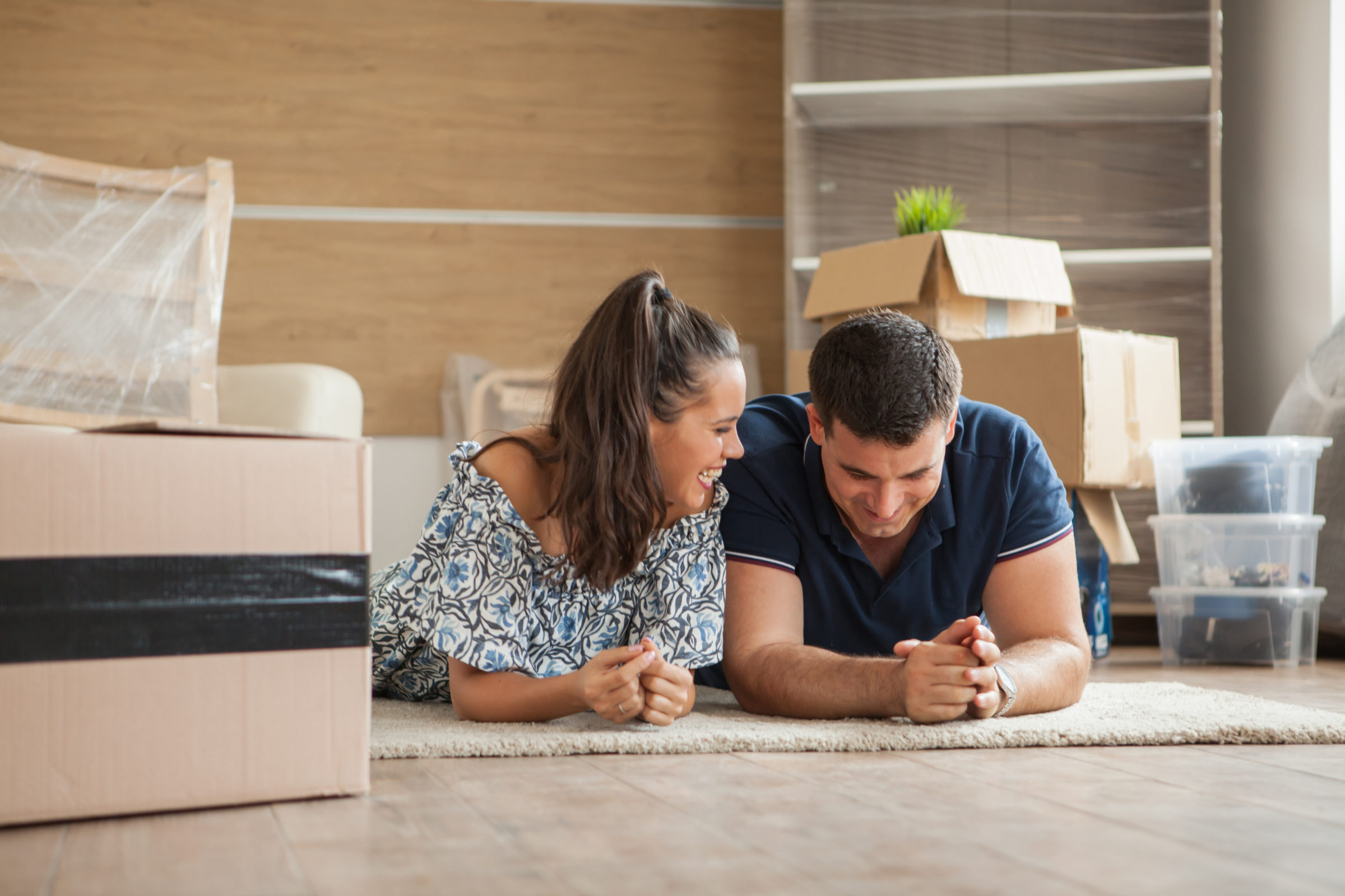 couple moving in house sitting on the floor X9L83AC