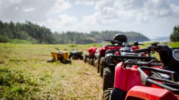 focus photography of ATV's falling in line on grass field