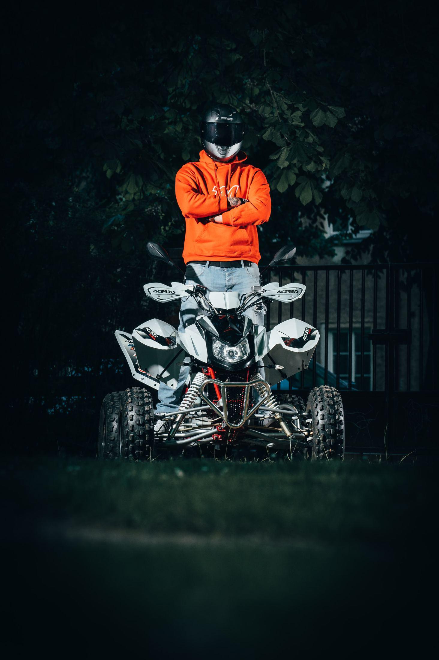 man in orange jacket riding white and black motorcycle